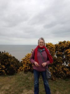 Rachel with gorse bushes and sea in background